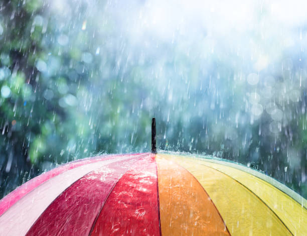 rain on rainbow umbrella - protection stock photos and pictures
