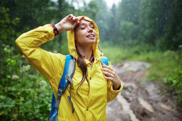 Rain pleasure Young woman with backpack enjoying rainy weather waterproof clothing stock pictures, royalty-free photos & images
