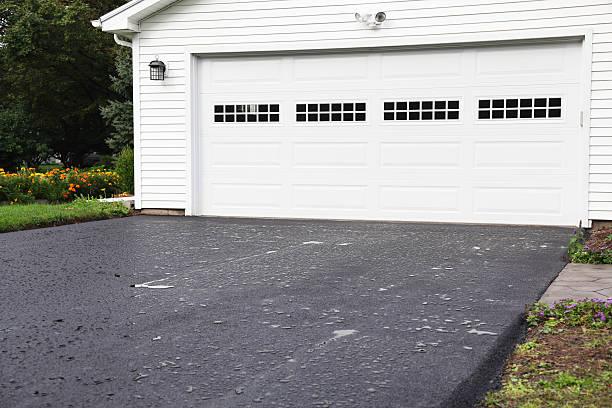 pfützen zu neuen asphalt straße in residential hause - auffahrt stock-fotos und bilder