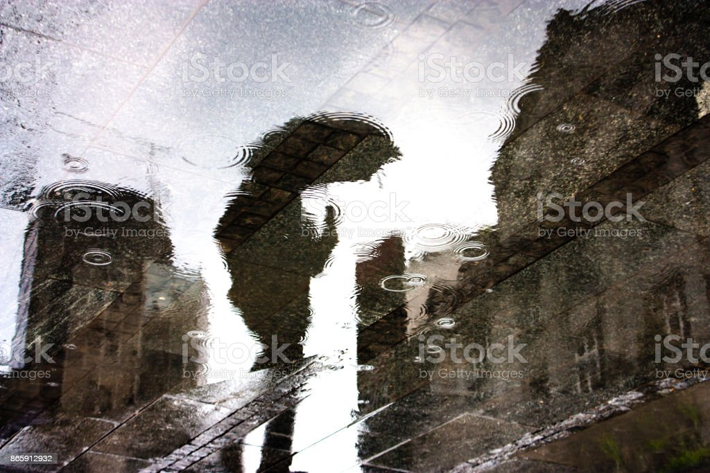 Rain reflection of a person in a puddle stock photo