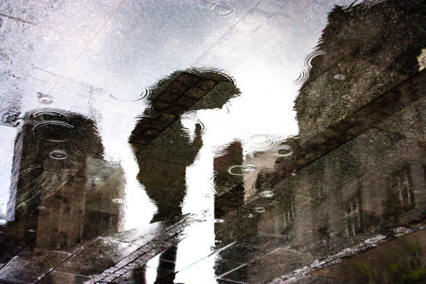 水たまりに人の雨反射 - 背景に人 ストックフォトと画像