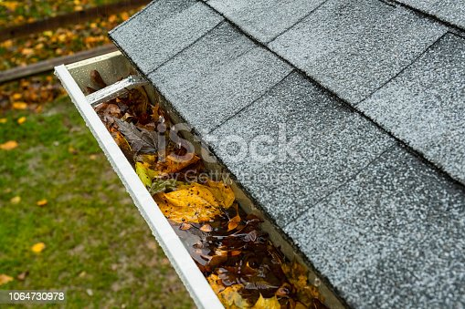 Close-up of rain dripping into aluminum seamless gutters that is clogged with Autumn leaves as it runs off the new architectural shingles on a residential house.