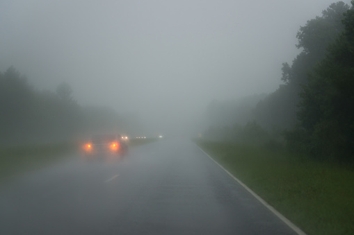 Rain shower on highway with red taillights and white front lights of other cars.