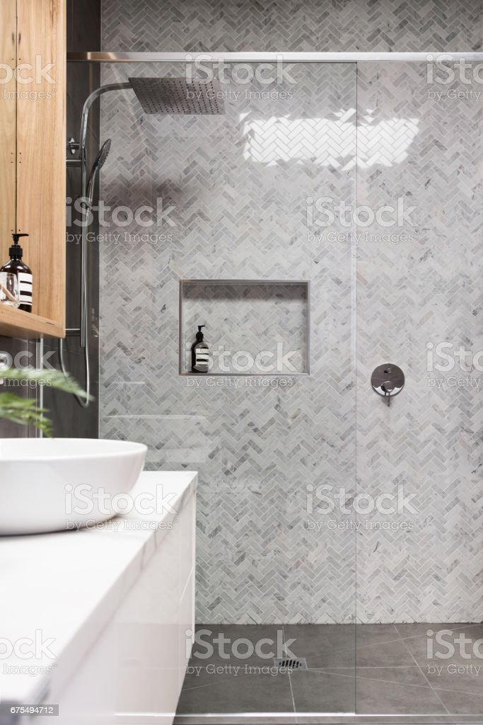Rain shower with herringbone marble feature tile wall stock photo