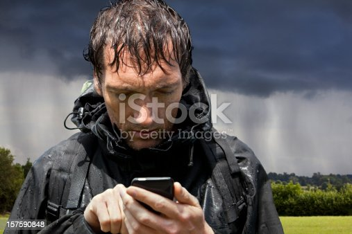 Backpacking hiker soaked by passing rainstorm looking at touchscreen GPS smartphone, for sat nav map app directions or looking at emails etc.