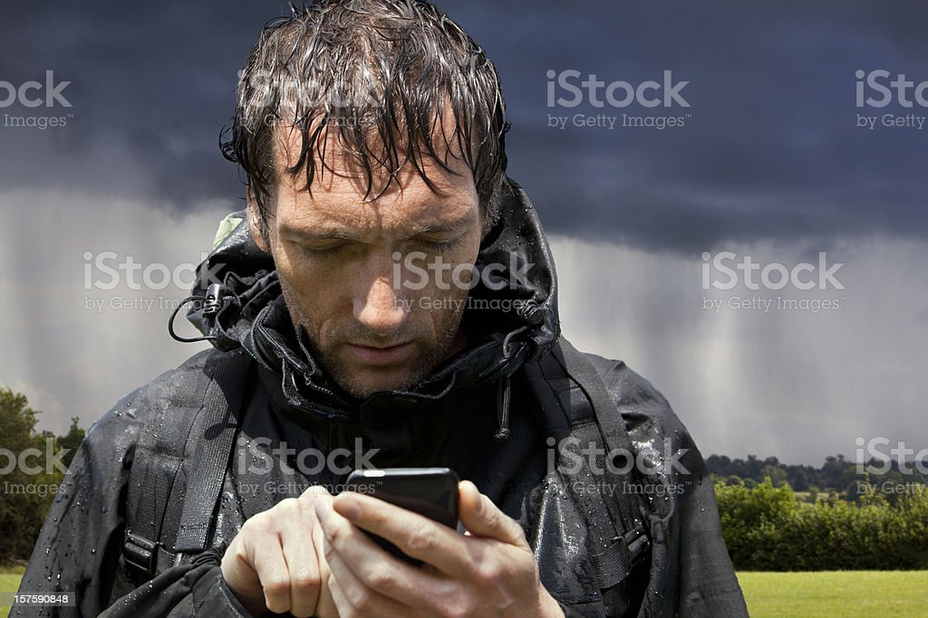 Rain Soaked Hiker Consults Touchscreen GPS Smartphone stock photo