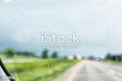 1054750504 istock photo Rain Storm Splattered Raindrops on Speeding Car Blurry Windshield 494559184