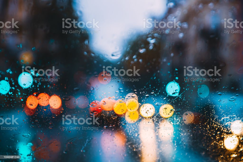 Rain Water Drops On Blue Glass Background In Night Or Evening Street...