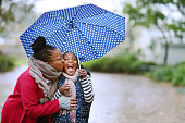Shot of woman kissing her daughter under an umbrella