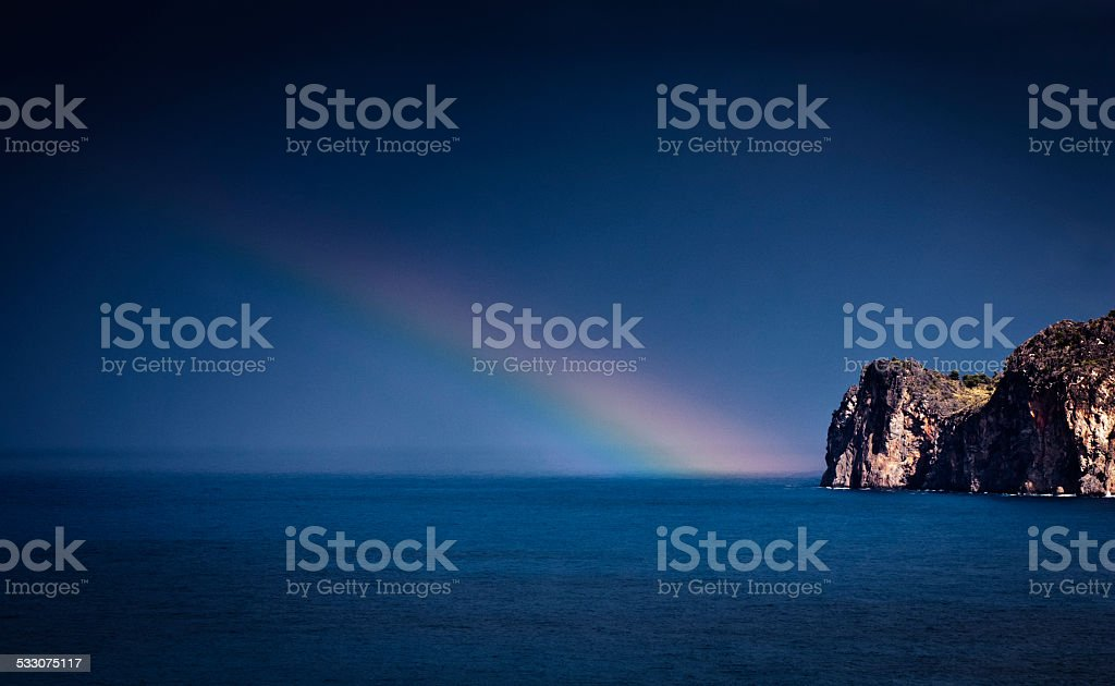 Rainbow across blue sea at Cala Deia on Mallorca island stock photo