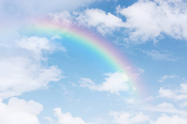 rainbow across in the blue sky after the rain stock photo