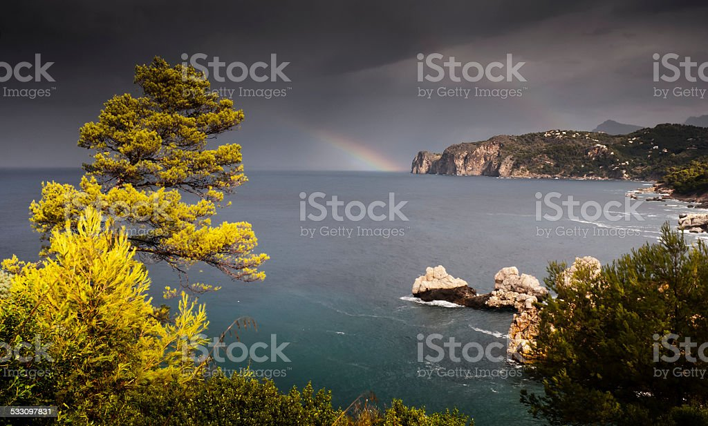 Rainbow across sea at Cala Deia on balearic island Mallorca stock photo
