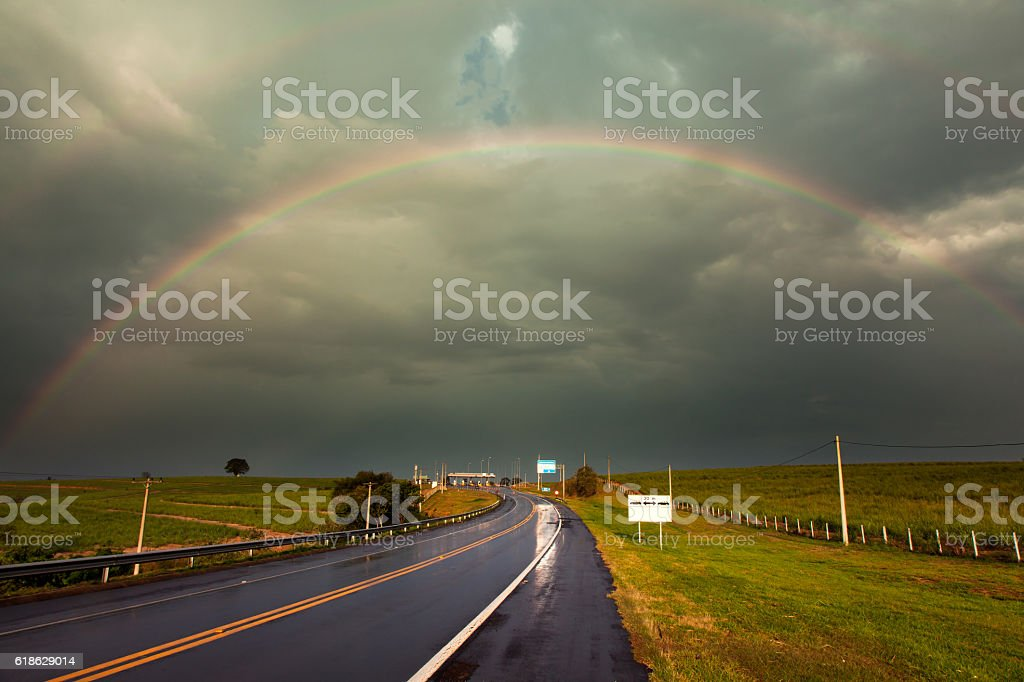 Rainbow after a storm in a wet highway stock photo