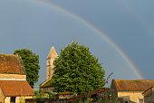 Rainbow after the rain over the church in Taizé, Burgundy