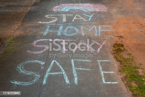 Rainbow and Stay Home Stay Safe chalk drawings on pavement during Covid19 in UK.