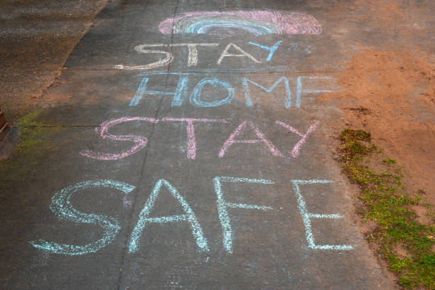 Rainbow and Stay Home Stay Safe chalk drawings on pavement during Covid19 in UK. Rainbow and Stay Home Stay Safe chalk drawings on pavement during Covid19 in UK. chalk art equipment stock pictures, royalty-free photos & images