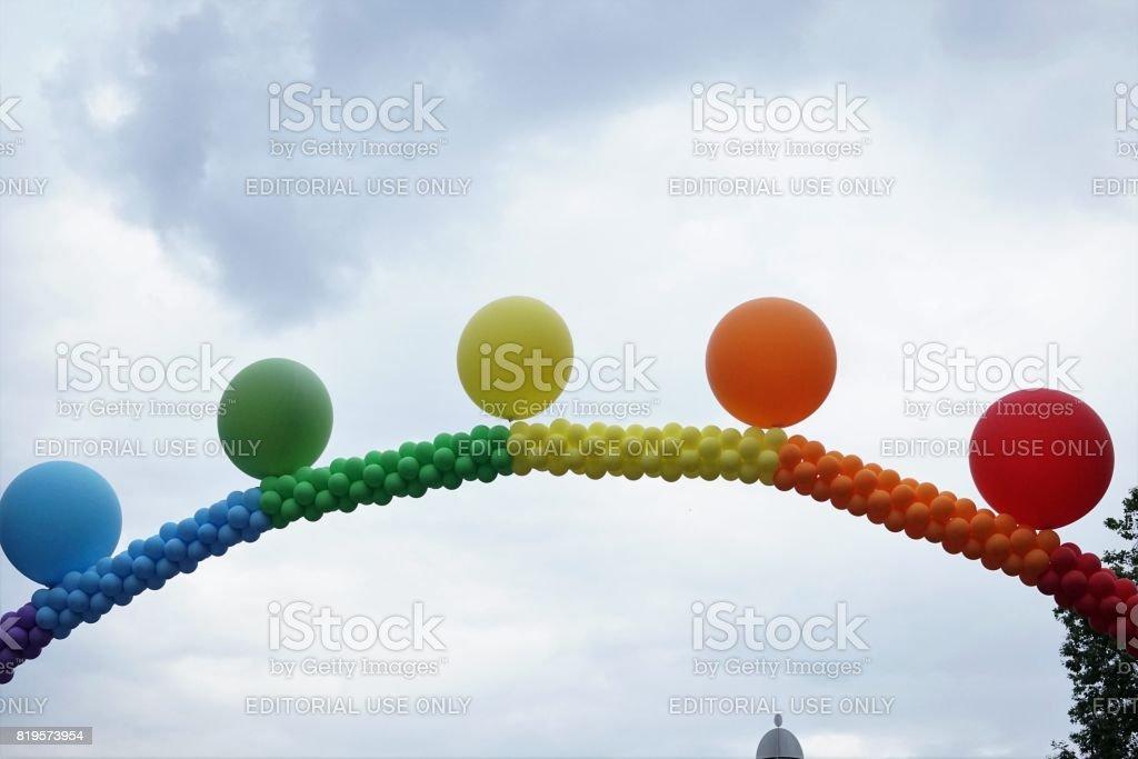 Rainbow balloon arch against cloudy sky stock photo