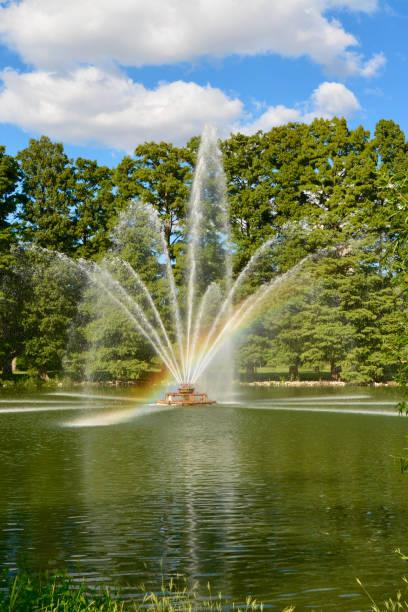 Rainbow Beam of Light from Fountain in Park stock photo