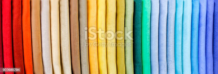 istock Rainbow clothes background. Pile of bright folded clothes. 922685294
