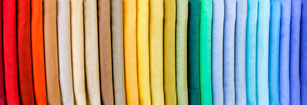 rainbow clothes background. pile of bright folded clothes. - textile stock photos and pictures