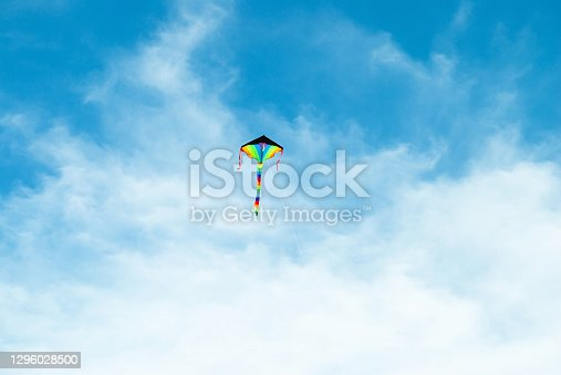 istock Rainbow color bright kite toy flying high up in blue sky background 1296028500
