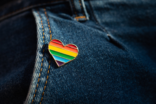 Rainbow color lgbt heart badge on jeans. Closeup photo. Freedom concept parade.