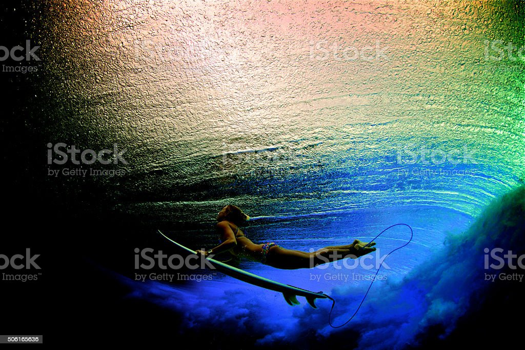 Rainbow colored duck dive of surfer girl stock photo