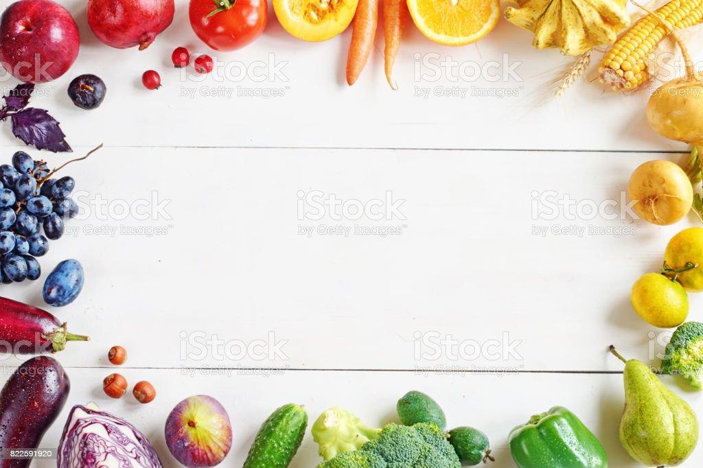 Regenbogenfarbenen Obst und Gemüse auf einem weißen Tisch mit Textfreiraum. – Foto