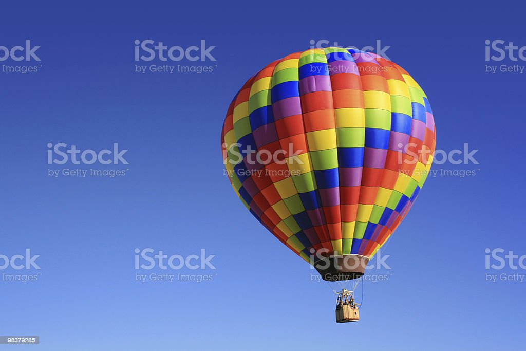 Rainbow colored hot air balloon in the blue sky royalty-free stock photo