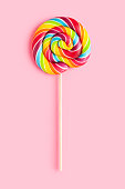 Rainbow colored lollipop on pink background. This file is cleaned and retouched.