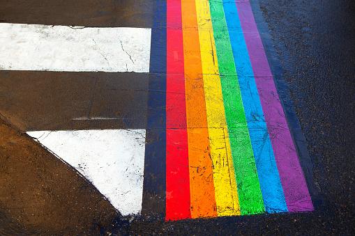 Rainbow colored pedestrian crossing . Road markings in the Parisian Marais