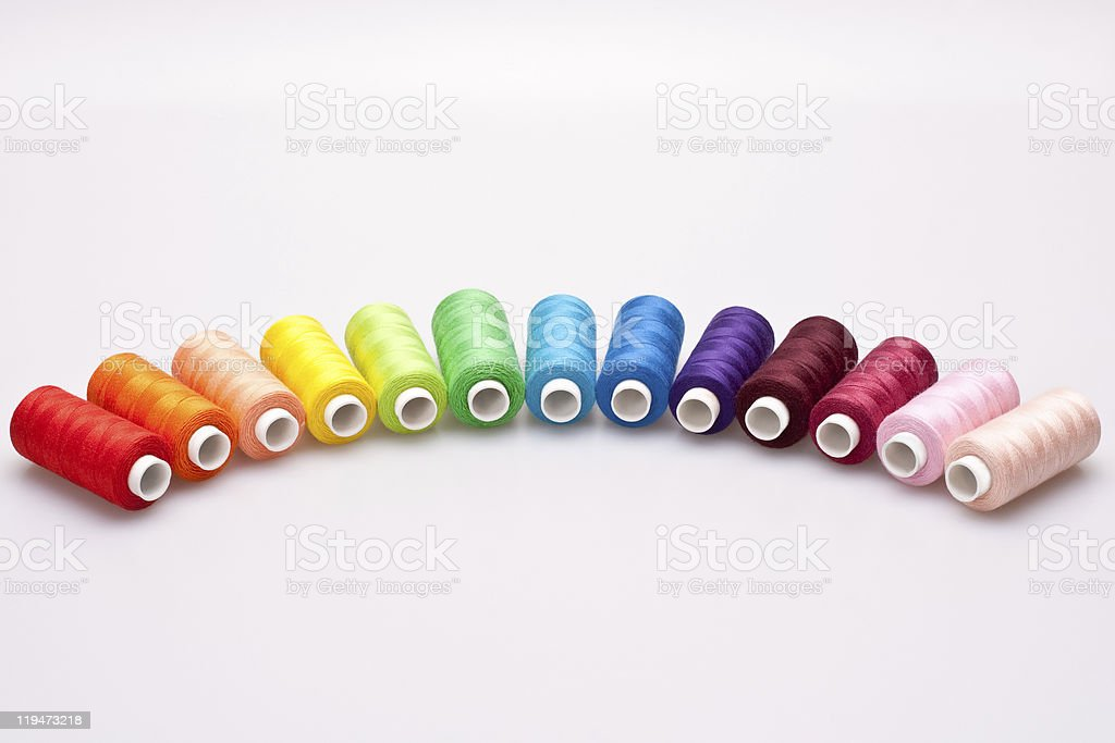 Rainbow colored sewing thread lined in a row stock photo