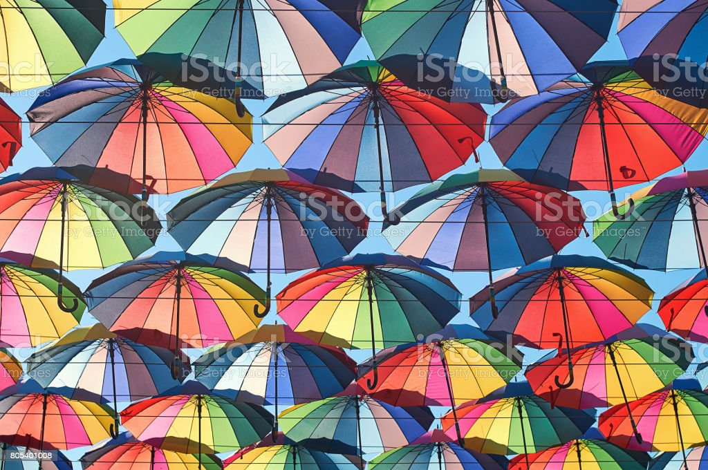Rainbow colored umbrellas over the street stock photo