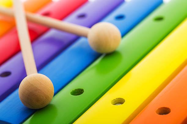 regenbogen farbige holz spielzeug xylophon vor weißem hintergrund - lautbildungsspiele stock-fotos und bilder