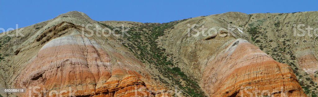 Rainbow colorful mountains with the green grassy slopes stock photo