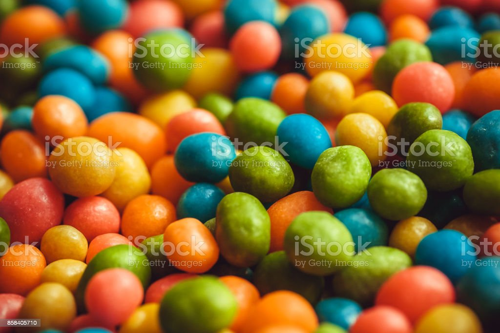 Rainbow colors on background of bright candy small round forms. Abstract sweets with raisins or nuts stuffing stock photo