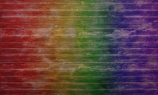 Wood planks with worn off surface painted in rainbow colors