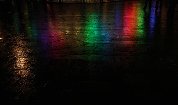 Rainbow colors reflected on wet street at night stock photo