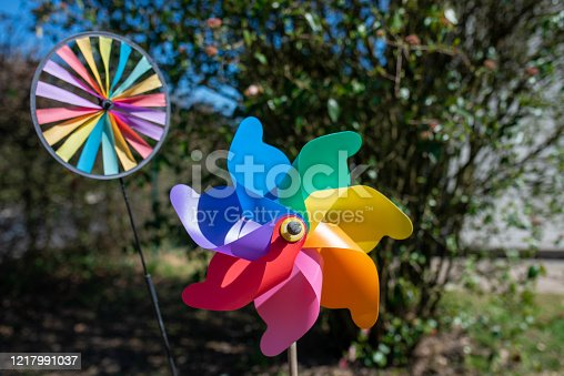 Rainbow coloured Windmill Garden decorations for kids, spinning in the springtime wind