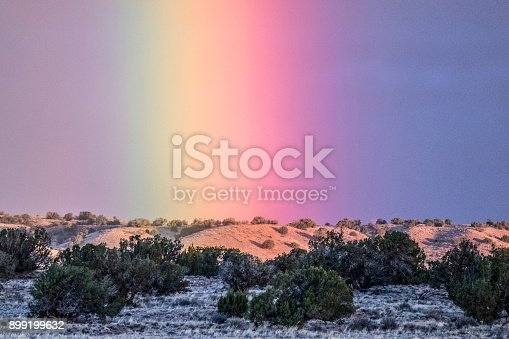 Telephoto shot of a rainbow to the west at dawn. Eastern Arizona high desert. American Southwest.