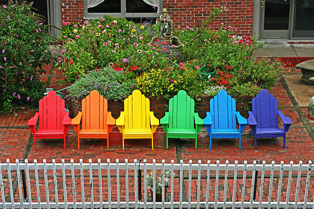 Rainbow Deck Chairs Rainbow colored deck chairs on a brick patio in Provincetown, backed by flowers. provincetown stock pictures, royalty-free photos & images