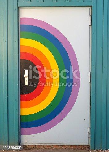 Rainbow door in wooden wall
