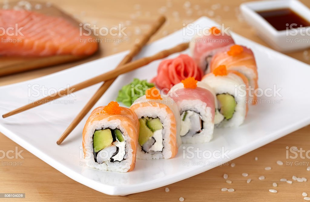 Rainbow dragon sushi roll with salmon, avocado, soft cheese, cucumber Rainbow dragon sushi roll with salmon, avocado, soft cheese, cucumber and tobiko caviar. Traditional asian rice sushi healthy seafood. White plate, wooden table background. Appetizer Stock Photo