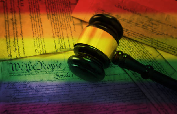 Rainbow flag gavel on America's Constitution Court gavel on rainbow flag colored pages of the United States Constitution  -- gay rights concept sex discrimination stock pictures, royalty-free photos & images