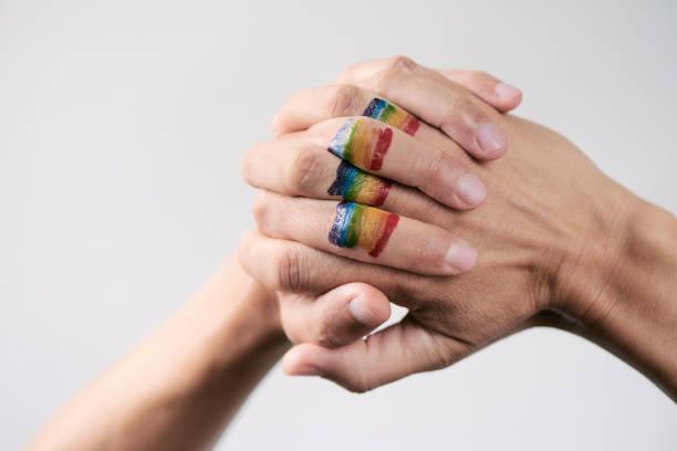 """人の握りしめ手に虹の旗 - """"gender fluid"""" ストックフォトと画像"""