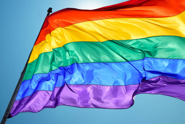 Rainbow flag on clear sky symbol of tolerance and acceptance Rainbow Flag consists of six stripes, with the colours red, orange, yellow, green, blue, and violet lgbtqi rights stock pictures, royalty-free photos & images