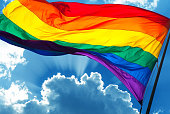 Rainbow flag on cloudy sky background