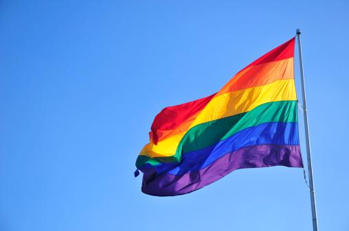 Rainbow flag over blue sky.