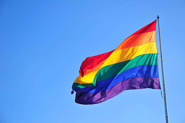 Rainbow flag Rainbow flag over blue sky. lgbtqi people stock pictures, royalty-free photos & images