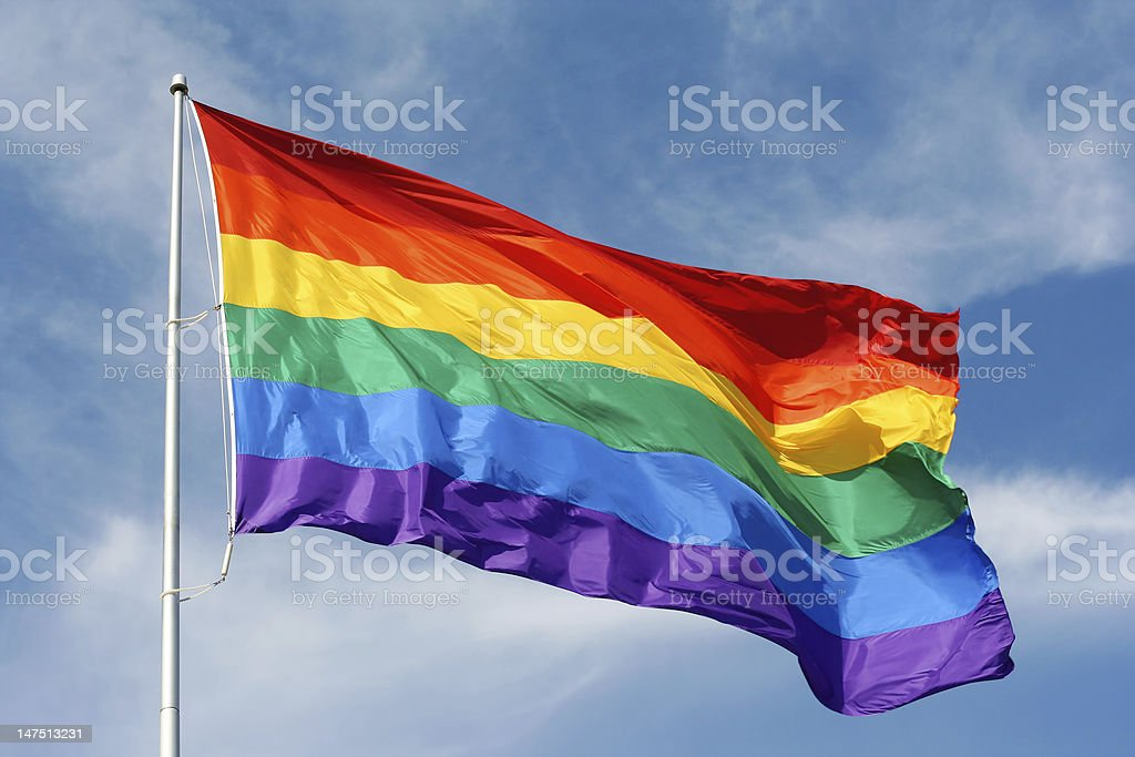 Rainbow flag proudly waving stock photo